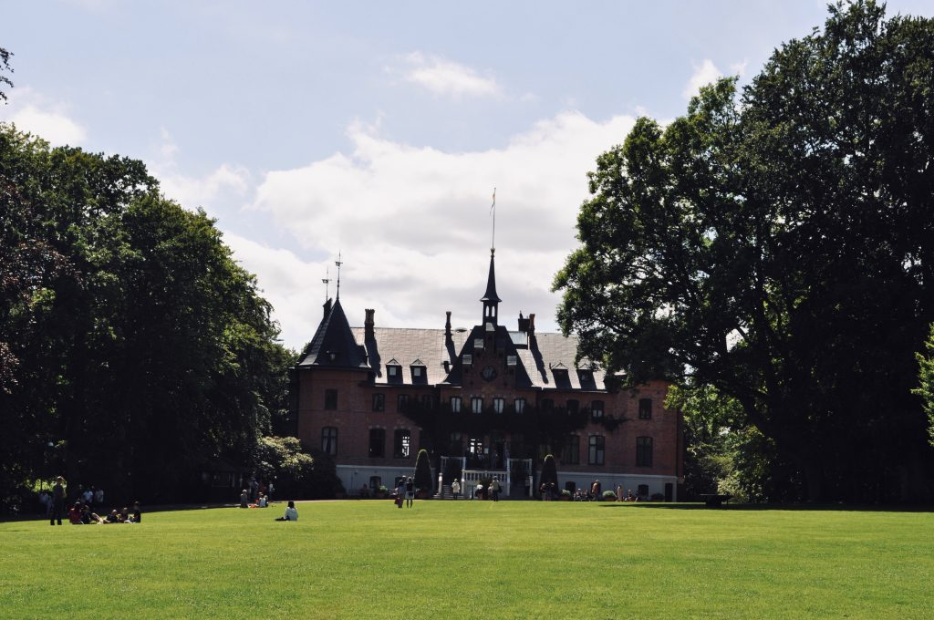 Photo showing a summer castle surrounded by trees and a green open area