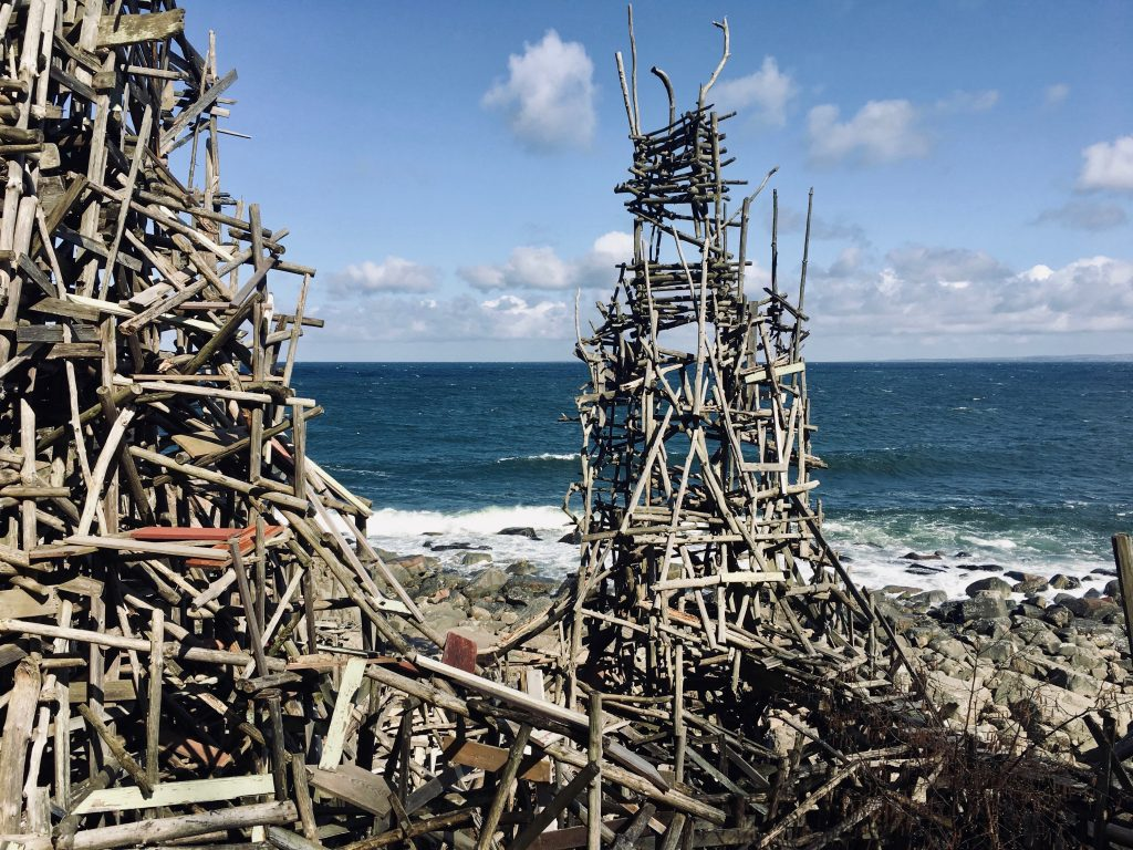 Wooden castle-like sculpture with sea in the background